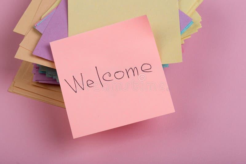 приветствующ концепцию - текст & x22; Welcome& x22; написанный вручную на стикере на розовой предпосылке стоковые фото