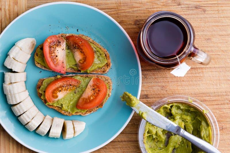 Приведите завтрак в действие с коренастым гуакамоле, отрезанными бананами и чаем стоковые изображения