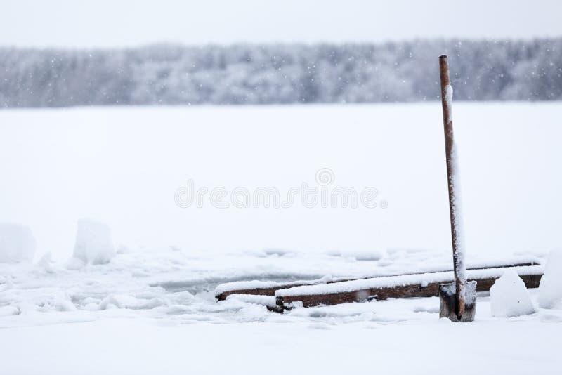 Прививать ручку лопаты в поле льда Делать лед-отверстие для плавания зимы в холодной воде стоковое изображение rf