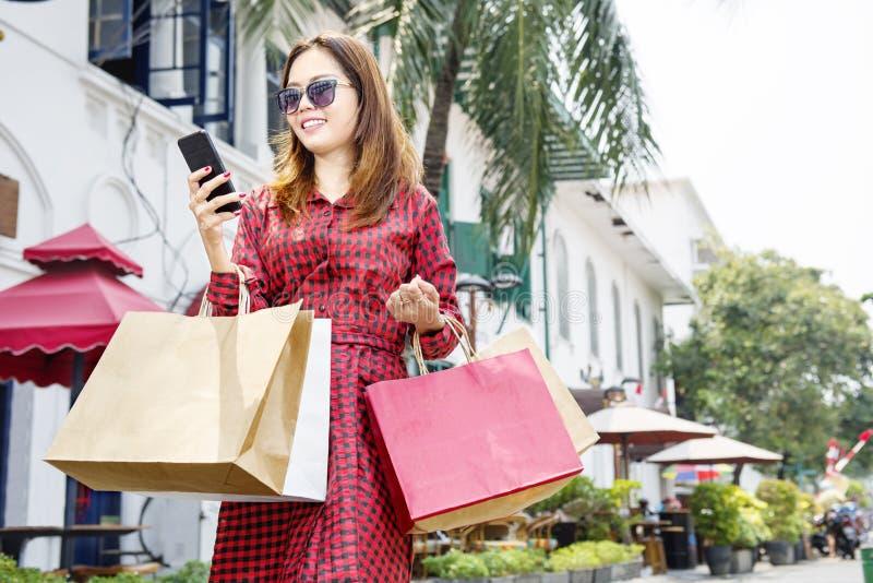 Привлекательная азиатская женщина используя мобильный телефон пока держащ ходить по магазинам стоковые фото