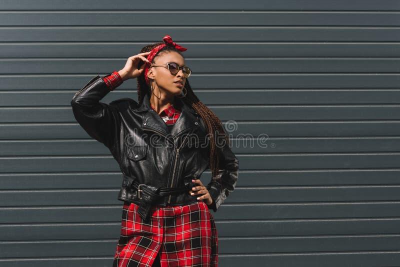 привлекательная Афро-американская девушка в модный кожаной смотреть куртки и солнечных очков стоковые фотографии rf