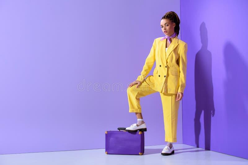 привлекательная Афро-американская девушка представляя в желтом костюме с фиолетовым чемоданом, на ультрамодном ультра стоковые фото