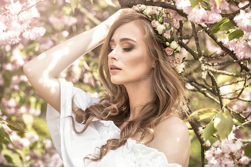 Привлекательная белокурая девушка в зацветая саде стоковые фото