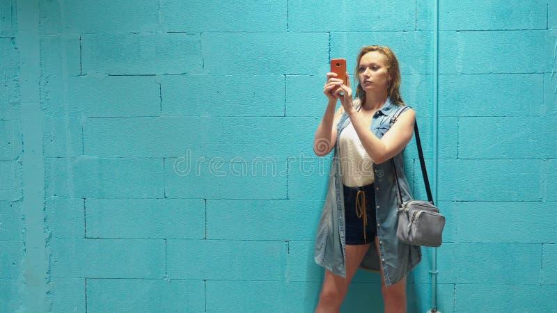 Привлекательная белокурая девушка использует красный смартфон против голубой стены стоковые фотографии rf