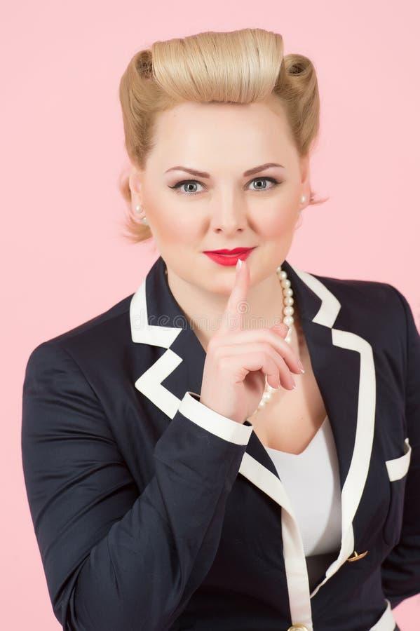 Привлекательная белокурая девушка с стилем причёсок штыря-вверх курчавым с пальцем на ее красных губах заволакивание предпосылки  стоковое изображение rf
