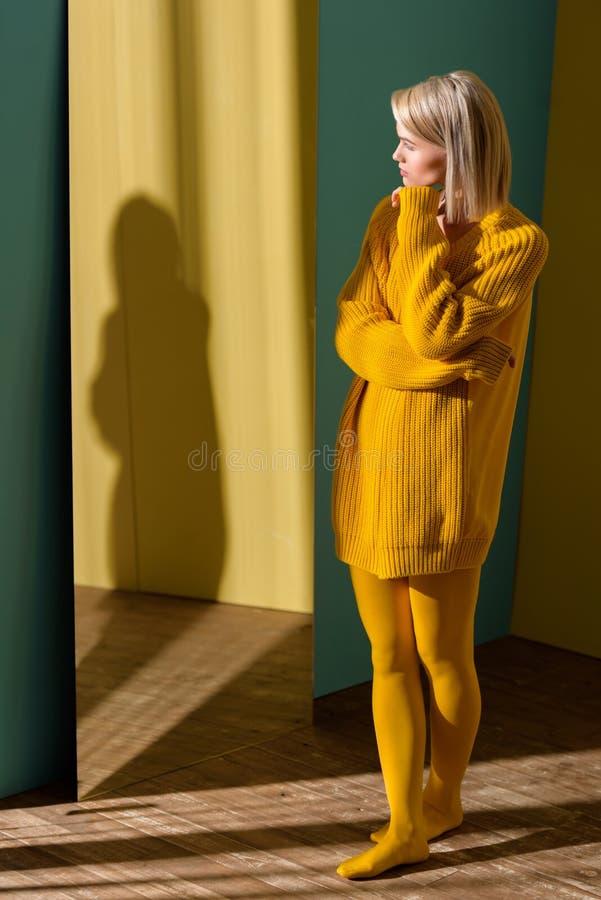 привлекательная белокурая женщина в желтом положении свитера и колготков стоковые изображения rf
