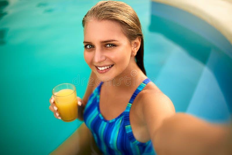 Привлекательная белокурая женщина при длинные волосы сидя на poolside и принимая портрет selfie с камерой мобильного телефона дев стоковое фото rf