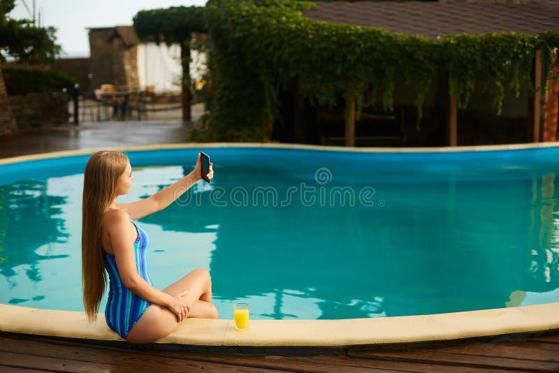 Привлекательная белокурая женщина при длинные волосы сидя на poolside и принимая портрет selfie с камерой мобильного телефона дев стоковая фотография rf