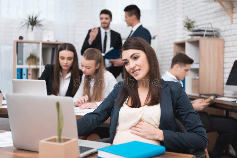 Привлекательная беременная девушка работает в офисе с коллегами Беременная коммерсантка в месте для работы материнствй стоковые изображения