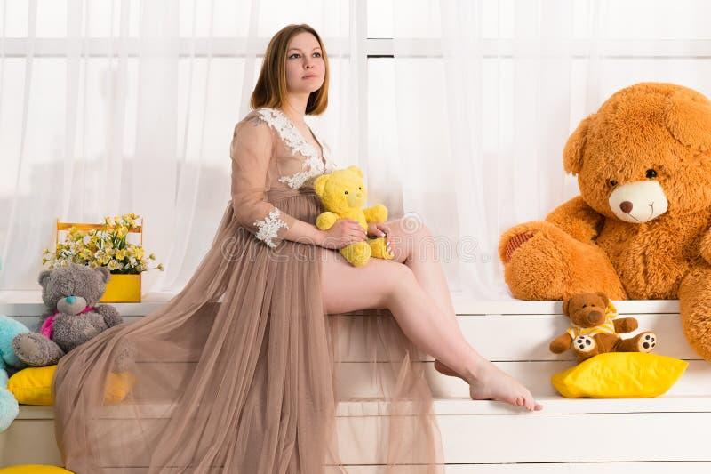 Привлекательная беременная женщина с игрушкой в руках стоковое изображение rf
