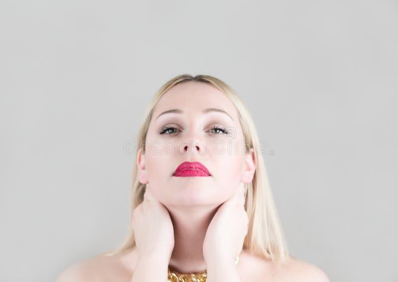 Привлекательная блондинка молодой женщины на серых backgounds студии стоковая фотография