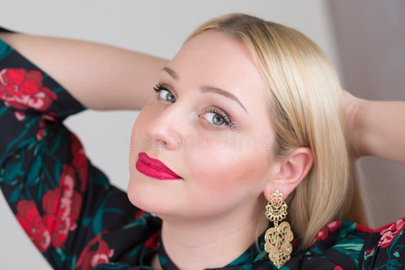 Привлекательная блондинка молодой женщины на серых backgounds студии стоковые фото