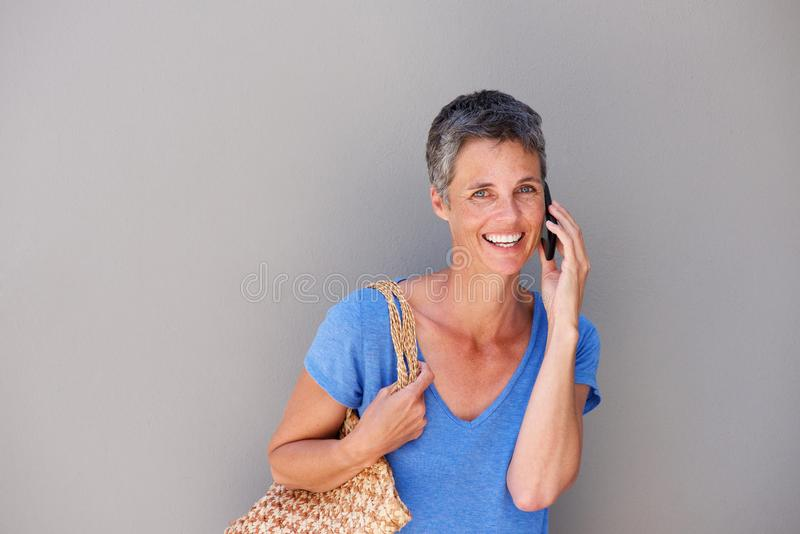 Привлекательная более старая женщина говоря на мобильном телефоне стоковые изображения rf