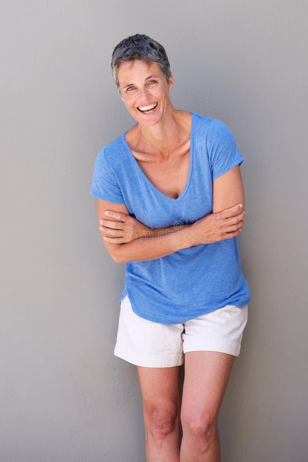Привлекательная более старая женщина смеясь над против серой стены стоковое фото rf