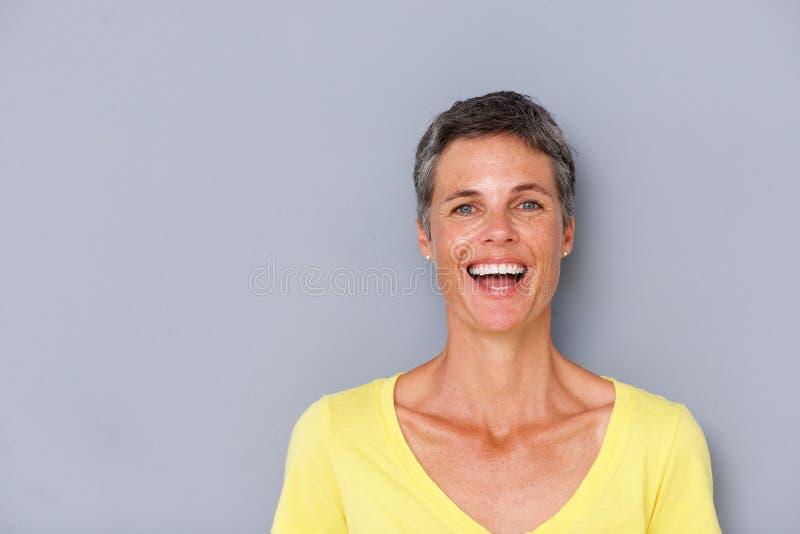 Привлекательная более старая женщина смеясь над серой стеной стоковое изображение