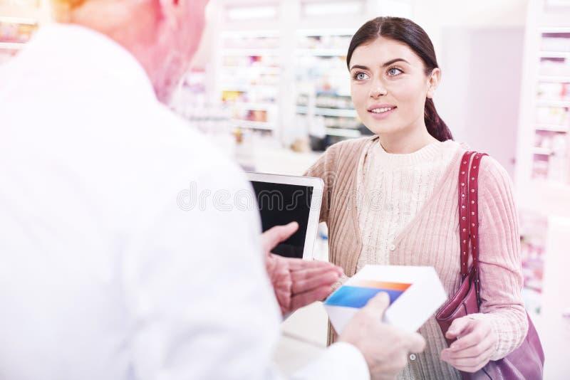 Привлекательная голубоглазая женщина слушая умный druggist стоковое фото