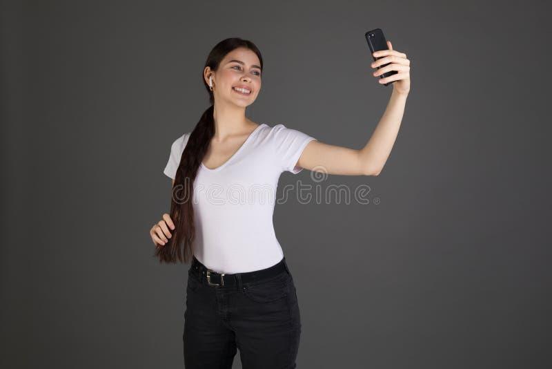 Привлекательная девушка брюнета в белой футболке над серой предпосылкой, смотря усмехаться мобильного телефона стоковая фотография rf