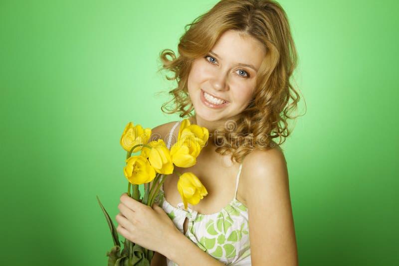 привлекательная девушка букета обнимая желтый цвет тюльпанов стоковое фото