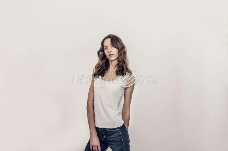 Привлекательная девушка в белой футболке с вьющиеся волосы стоковое изображение
