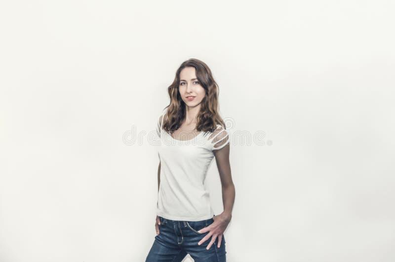Привлекательная девушка в белой футболке с вьющиеся волосы стоковое фото rf
