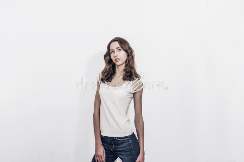 Привлекательная девушка в белой футболке с вьющиеся волосы стоковое фото
