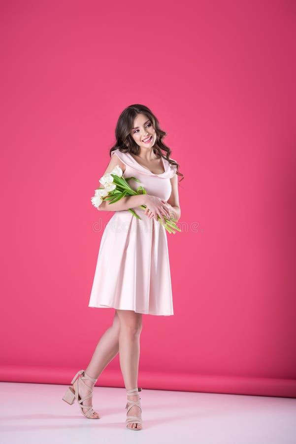 привлекательная девушка в розовом платье с букетом тюльпанов смотря прочь стоковая фотография