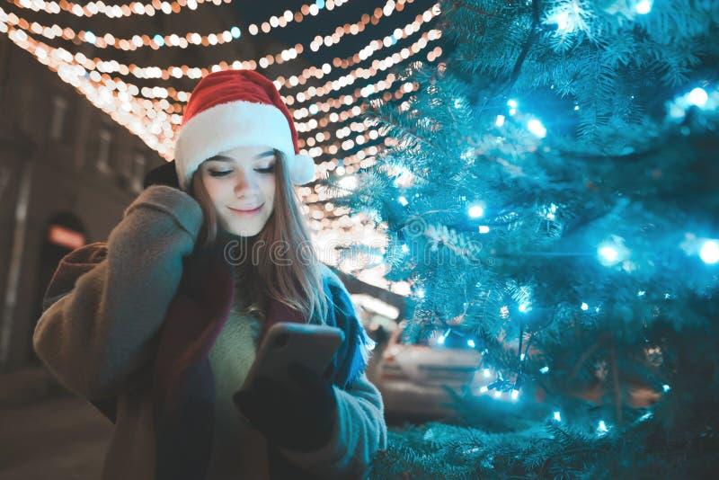 Привлекательная девушка в шляпе рождества стоит в рождественской елке улицы, смартфоне в ее руках стоковая фотография rf