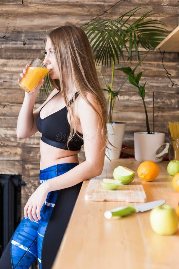 Привлекательная девушка в sportswear подготавливает здоровый завтрак перед разминкой в кухне, плоде отрезков и напитках стоковые изображения