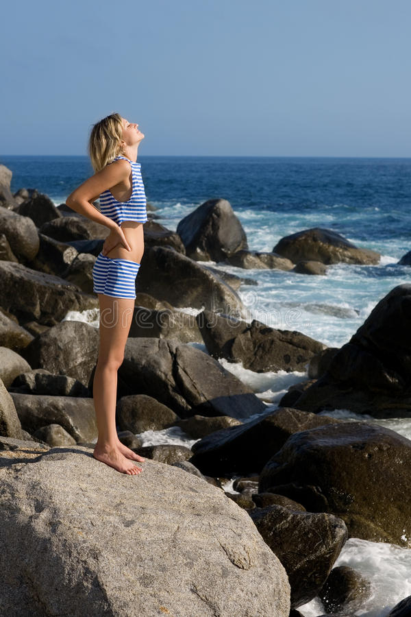 привлекательная девушка пляжа ослабляя утесистое море стоковые изображения rf