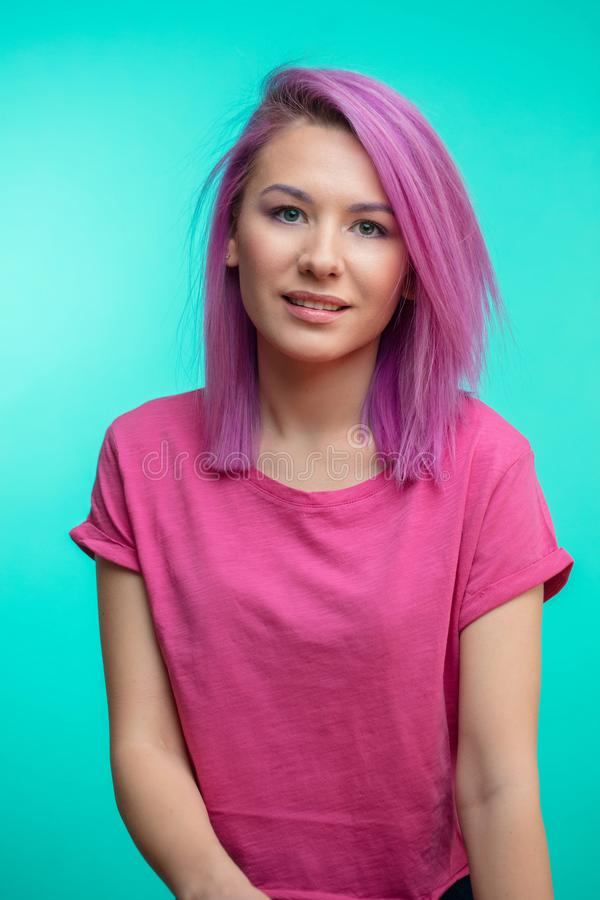Привлекательная девушка при розовые волосы, одетые в вскользь розовой ткани на голубой предпосылке стоковые фотографии rf