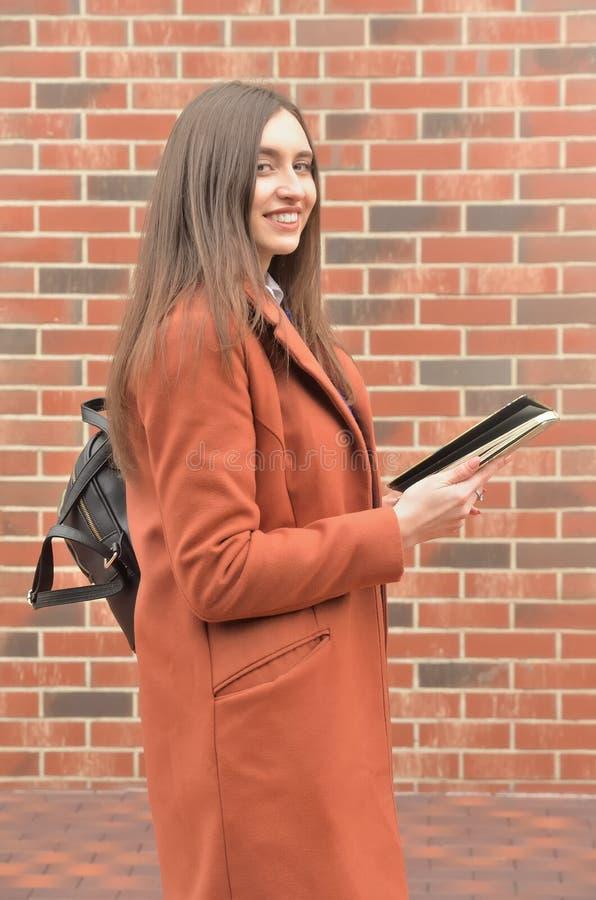 Привлекательная девушка стоит на фоне кирпичной стены стоковое фото rf