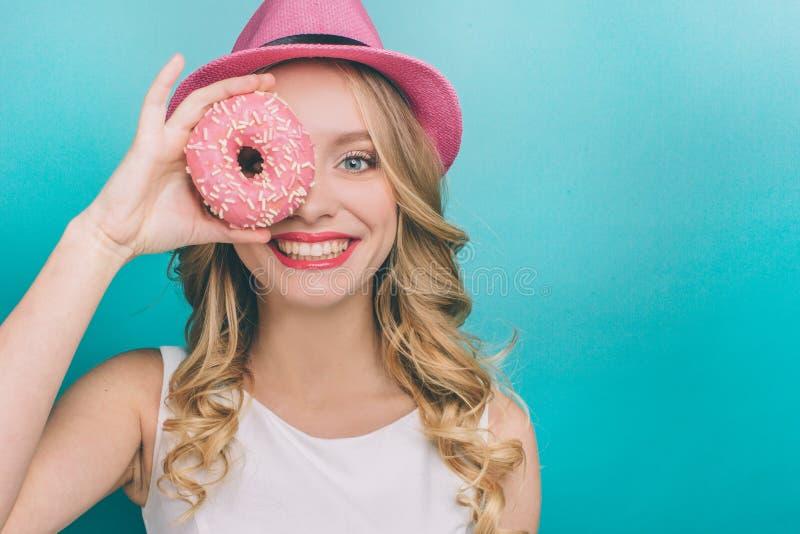 Привлекательная девушка с белокурыми волосами смотрит прямой и усмехаться Она покрывает одно из ее глаза с донутом с пинком стоковое изображение rf