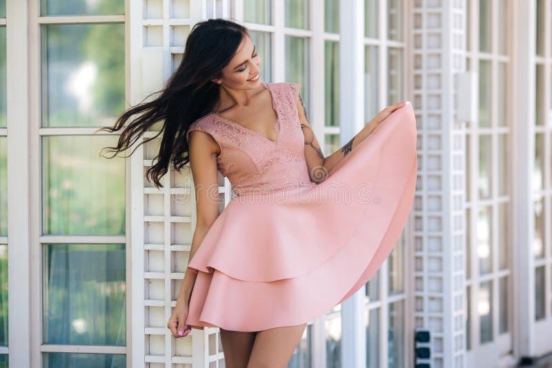 Привлекательная девушка с красивой улыбкой в розовом платье позирует в уличном кафе стоковые фотографии rf