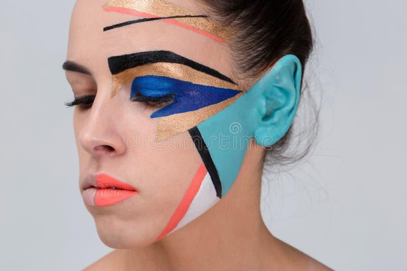 Привлекательная девушка, с красочным творческим геометрическим гримом на ее стороне смотрит вниз стоковые изображения rf