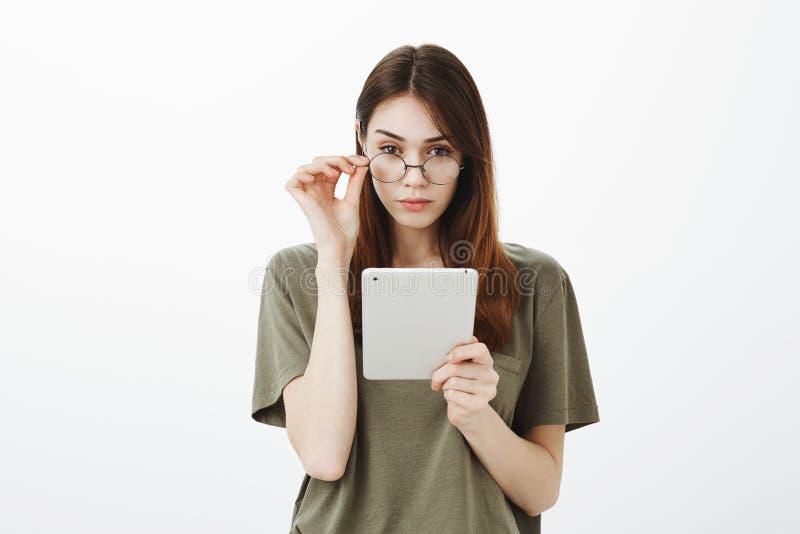 Привлекательная женская женщина с уверенно выражением, знает все Сфокусированное симпатичное брюнет с ультрамодными стеклами стоковое изображение rf