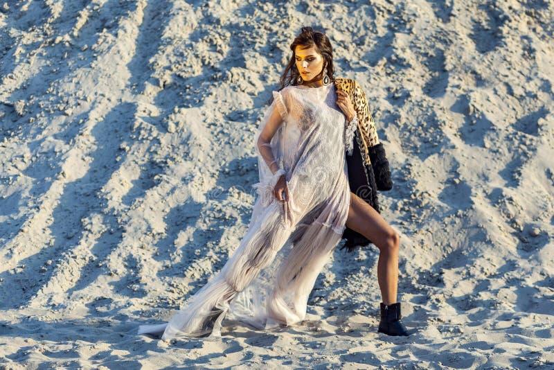 Привлекательная женщина брюнета в просвечивающем пляже покрывает с меховой шыбой леопарда представляя на песчаном пляже на заходе стоковые фотографии rf