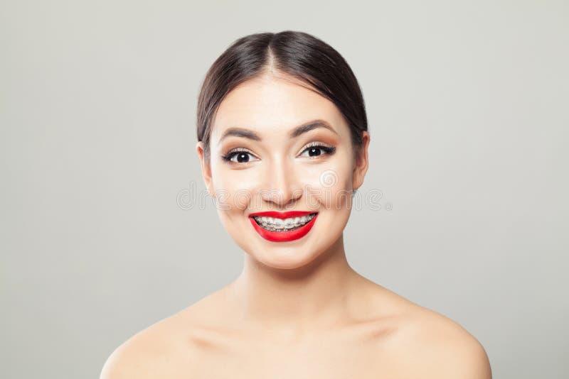 Привлекательная женщина брюнета в расчалках усмехаясь на белой предпосылке стоковые изображения rf