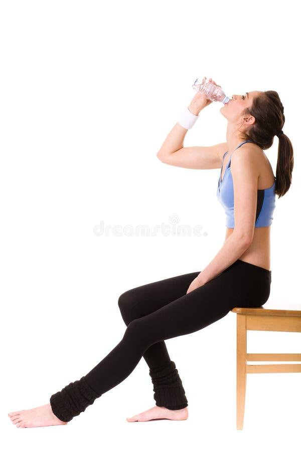 Привлекательная женщина в верхней части пригодности выпивает воду стоковое фото
