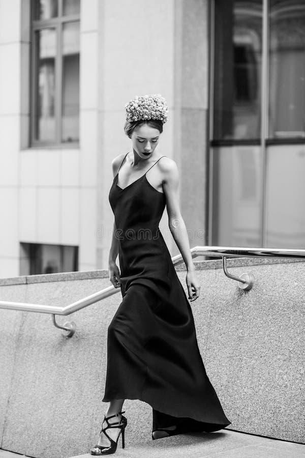 Привлекательная женщина в длинном платье черноты вечера представляя на шагах  стоковые изображения