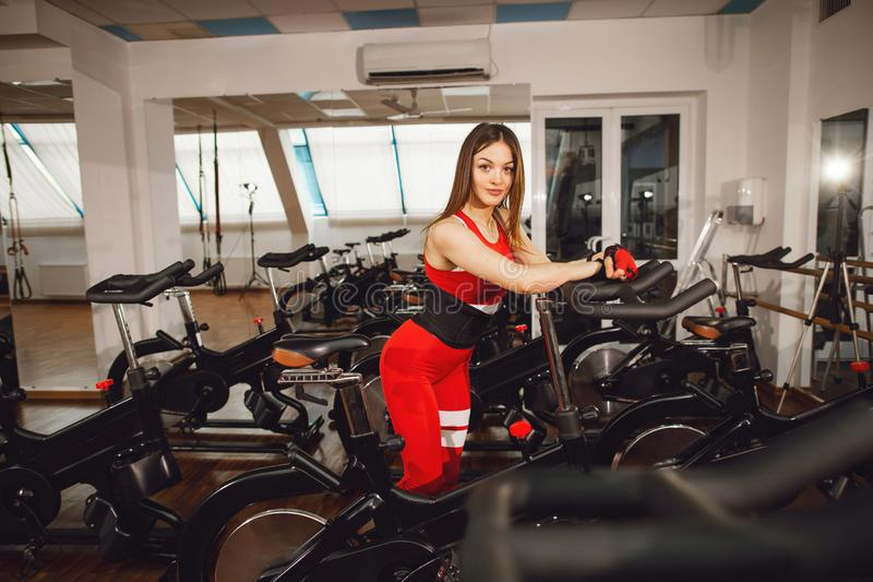 Привлекательная женщина в красном костюме спорт в спортзале, ехать на велосипеде скорости неподвижном o стоковое фото rf