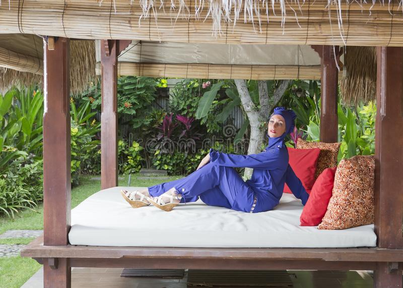 Привлекательная женщина в мусульманском burkini swimwear в газебо для остатков в саде стоковые фотографии rf