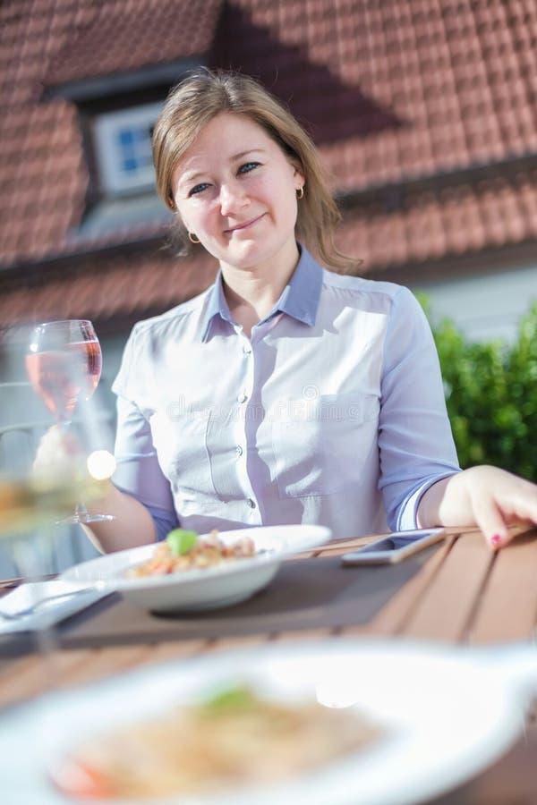 Привлекательная женщина есть завтрак на ее домашнем балконе стоковая фотография