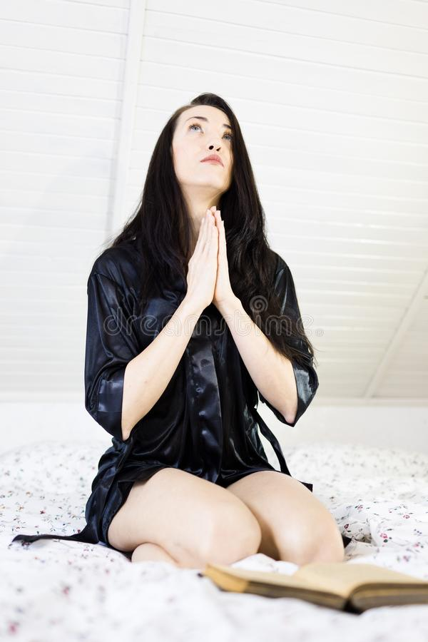 Привлекательная женщина моля в кровати с библией стоковая фотография rf