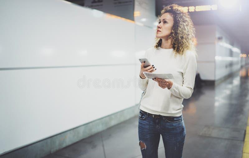 Привлекательная женщина на переходе используя smartphone пока идущ с рюкзаком ручного багажа в идти вокзала или airpot стоковое изображение