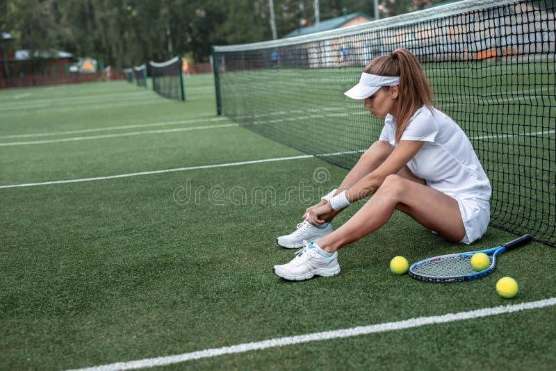 Привлекательная женщина на теннисном корте стоковое изображение rf
