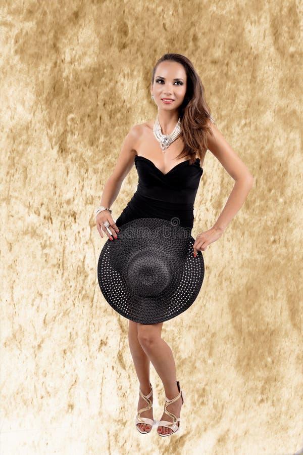 Привлекательная женщина нося черные платье, шляпу и жемчуга стоковые изображения rf