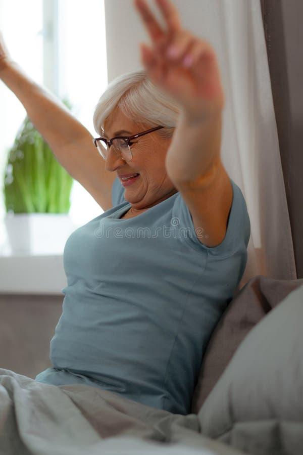 Привлекательная женщина поднимая ее руки пока сидящ в спальне стоковая фотография