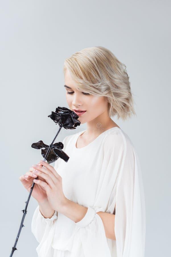 привлекательная женщина представляя в белой блузке с черной розой стоковые изображения rf