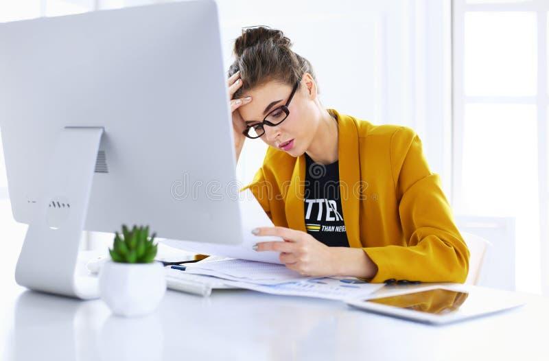 Привлекательная женщина сидя на столе в офисе, работающ с ноутбуком, держа документ стоковые изображения