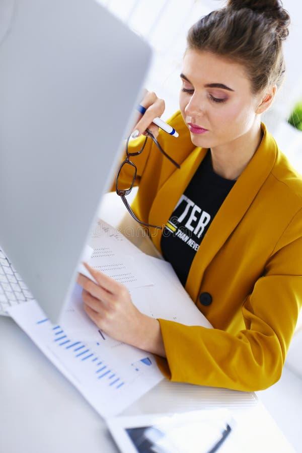 Привлекательная женщина сидя на столе в офисе, работающ с ноутбуком, держа документ стоковое фото rf